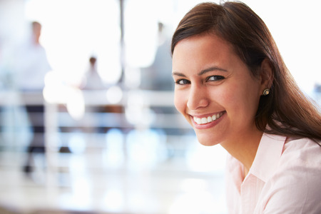 confident: Portrait of smiling woman in office