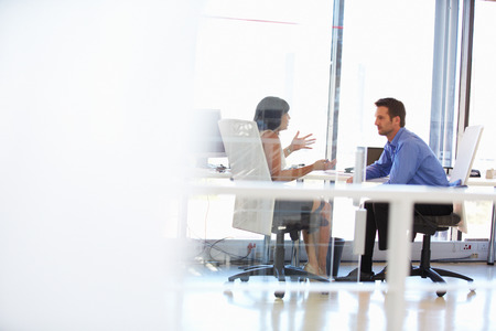people working together: Two people talking in an office Stock Photo