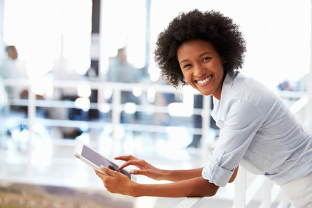 casual clothing: Portrait of smiling woman in office with tablet