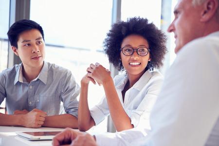 femmes souriantes: Trois professionnels d'affaires travaillant ensemble Banque d'images