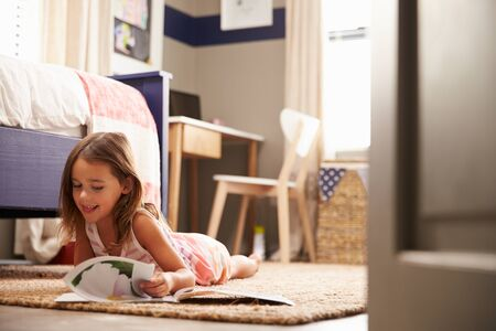 domestic life: Young girl lying on the floor reading