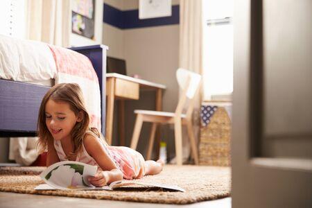 girl lying: Young girl lying on the floor reading
