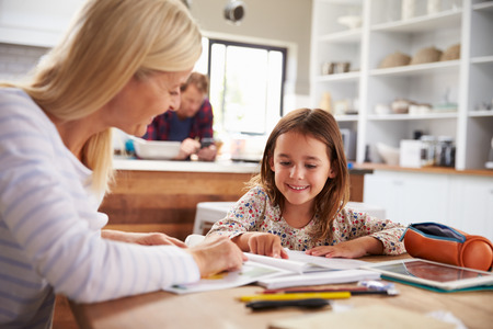 teaching children: Mother teaching her daughter at home