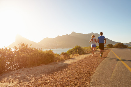 coastal: Man and woman running together on an empty road