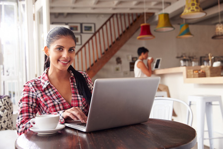 food woman: Young woman using laptop in a cafe