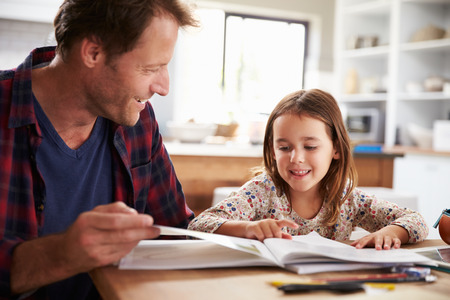 padres e hijos felices: Padre hogar que enseña a su pequeña hija