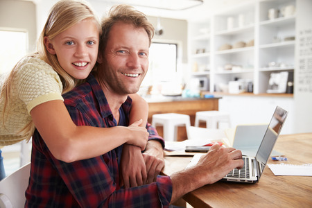 Girl hugging her father, working on laptop at home