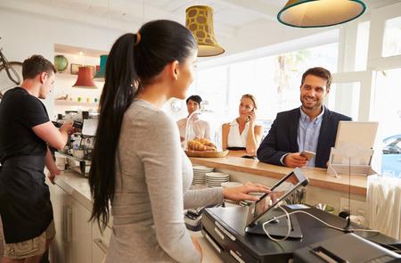 camarero: Ordenamiento Joven en el mostrador en un café