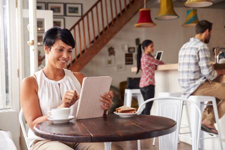 personas leyendo: Mujer de mediana edad en un café Foto de archivo