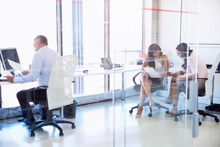 personas trabajando en oficina: Grupo de personas que trabajan en una oficina moderna