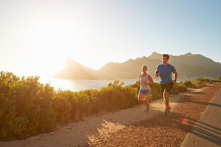 hombres corriendo: El hombre y la mujer corriendo juntos en una carretera vacía Foto de archivo