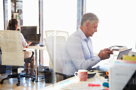 concentrating: Man at work using smart phone, office interior Stock Photo