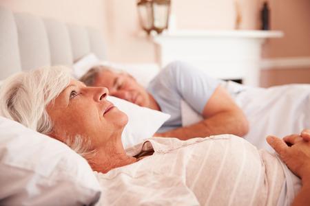 目を覚ましベッドで横になっている年配の女性を心配しています。 写真素材