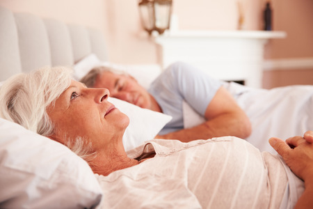 Worried Senior Woman Lying Awake In Bed Stock Photo