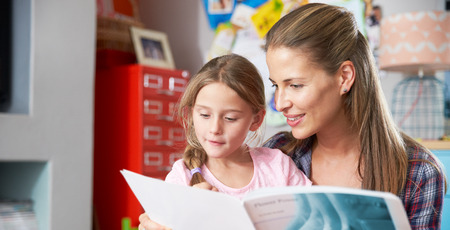 female child: Mother Reading Book With Daughter In Bedroom