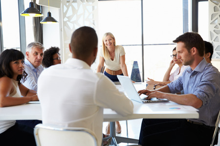 small room: Businesswoman presenting to colleagues at a meeting