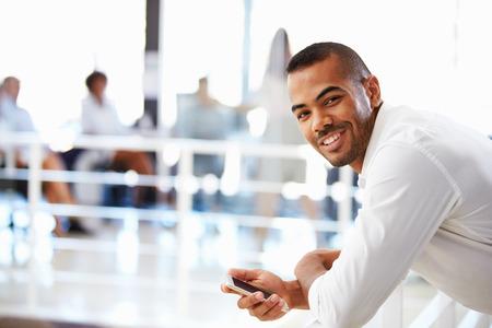 ejecutivos: Retrato del hombre en la oficina con teléfono, sonriendo