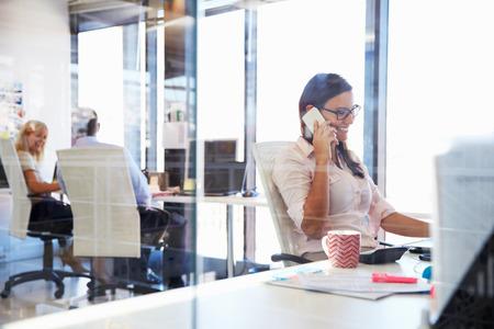 Frau im Gespräch mit dem Telefon auf ihrem Schreibtisch in einem Büro Standard-Bild - 41392810
