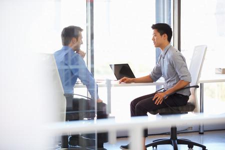 dos personas conversando: Dos hombres que trabajan en una oficina moderna