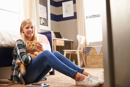 Girl holding pet cat in her bedroom photo