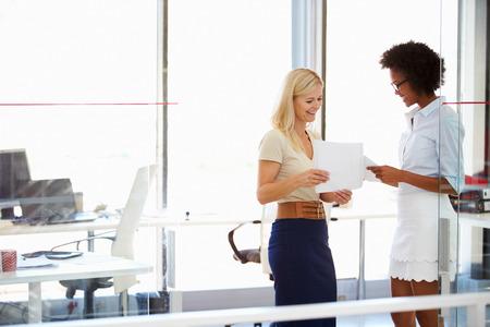 personas reunidas: Dos mujeres que hablan en una oficina moderna