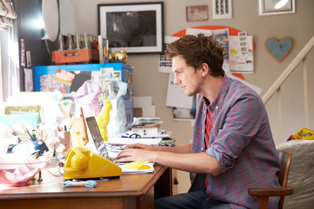 oficina desordenada: El hombre en la computadora port�til Running negocios desde casa Oficina