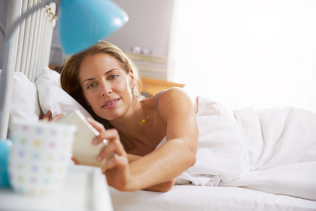 day bed: Woman Lying In Bed Reaching To Check Mobile Phone