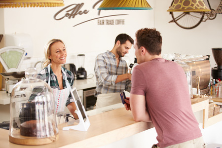business service: Young man paying for his order in a cafe Stock Photo