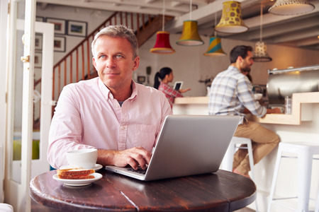 hombres trabajando: hombre de mediana edad usando la computadora portátil en un café