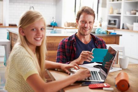 usando computadora: Padre e hija usando la computadora portátil en casa