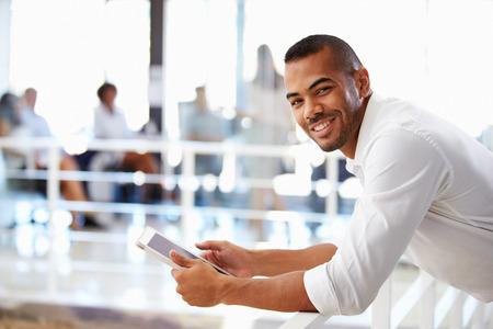 Portret van de man in het kantoor met behulp van tablet