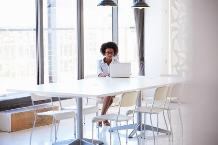 reunion de trabajo: Mujer joven que trabaja en la sala de reuniones vac�a