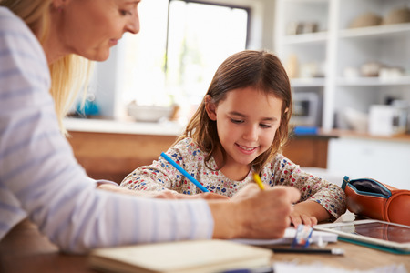 teaching and learning: Mother teaching her daughter at home