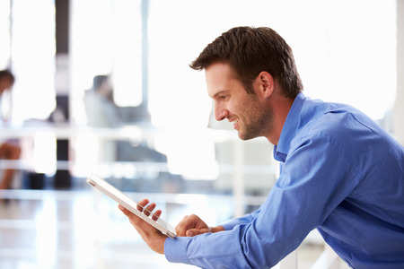 Portrait of man in office using tablet photo