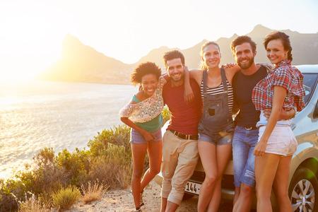 Groep vrienden die zich met de auto op de kust weg bij zonsondergang Stockfoto