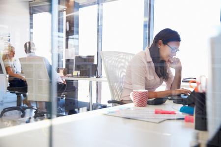 personas trabajando en oficina: Mujer que trabaja en la computadora en una oficina Foto de archivo