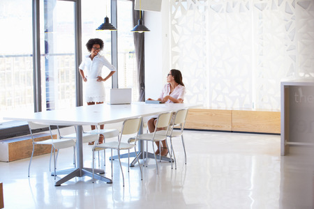 two people only: Two women working with digital tablet in empty meeting room