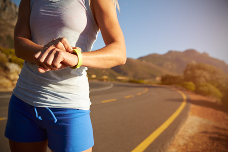 salud y deporte: Recortar foto de la mujer que controla su reloj deportivo