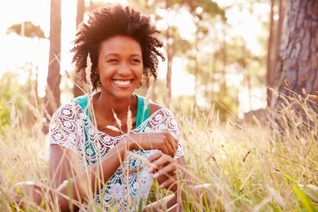 african american woman smiling: Portrait Of Smiling Young Woman Sitting In Countryside Stock Photo