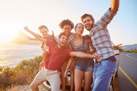 travel: Grupa przyjaciół stojących samochodem na nadmorskiej drodze Zachodzie Słońca