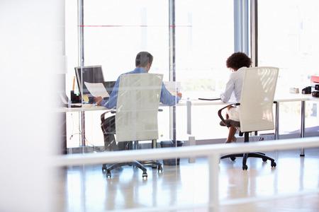 personas trabajando en oficina: Dos personas que trabajan en una oficina moderna