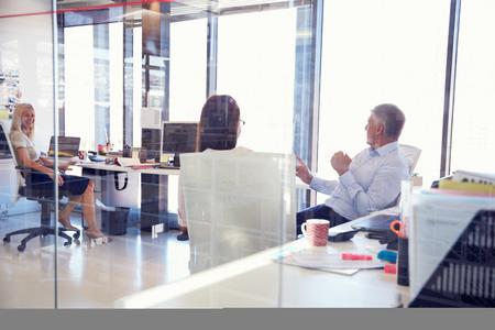 using the computer: Grupo de gente hablando en la oficina Foto de archivo
