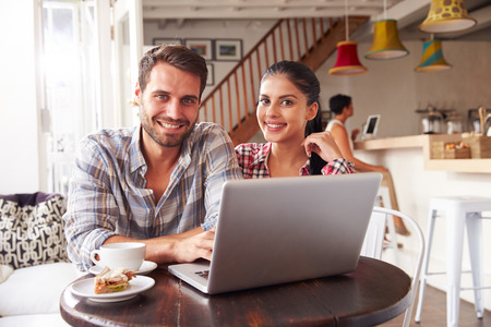 coffee shop: Young couple using laptop in a cafe Stock Photo