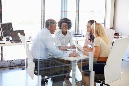 Cuatro colegas reunidos alrededor de una mesa en una oficina Foto de archivo - 41393021