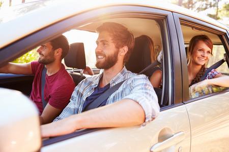 hombre manejando: Grupo de Amigos en coche en el camino de viaje Juntos