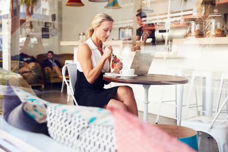 sitting down: Business woman sitting at a table in small coffee shop Stock Photo