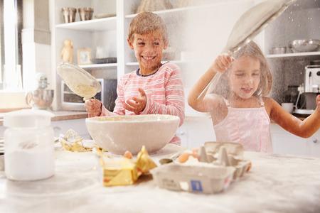 niños cocinando: Dos niños que se divierten de hornear en la cocina