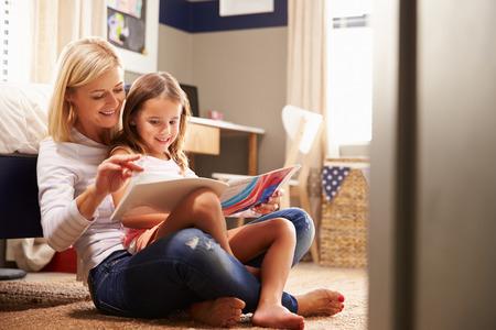 enfants: Mère lecture avec sa jeune fille