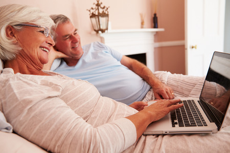 Senior Couple Lying In Bed Looking At Laptop Computer photo