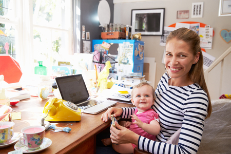 hija: Madre con la hija que ejecuta Small Business From Home Oficina Foto de archivo